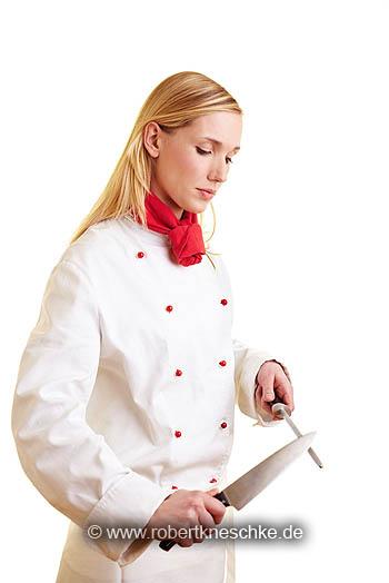 Köchin schleift Küchenmesser