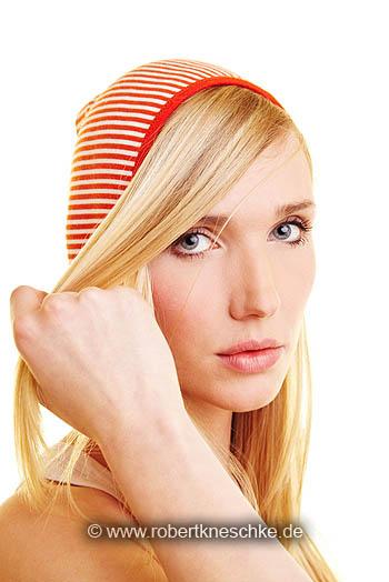 Blonde Frau streift Strähne aus dem Gesicht