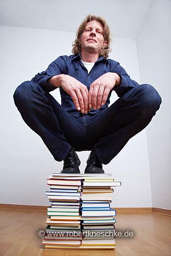 Auf Bücherstapel hocken