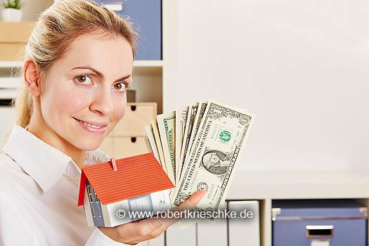 Frau als Makler mit Haus und Dollar