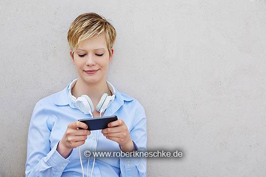 Junge Frau mit Kopfhörer nutzt Smartphone