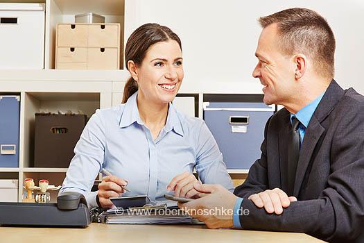 Steuerberater bei Finanzberatung im Büro mit Akten am Schreibtisch