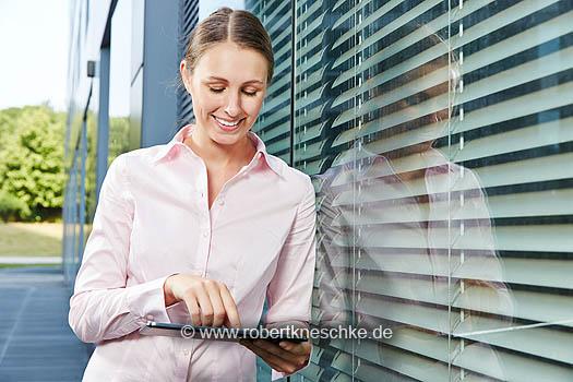 Junge Business Frau surft mit ihrem Tablet PC im Internet und nutzt Apps